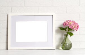 Empty white frame with pink hydrangea flowers